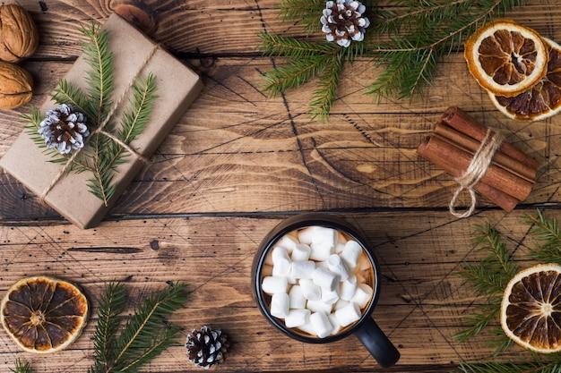 Chocolate quente com paus de canela marshmallow, anis, nozes na madeira