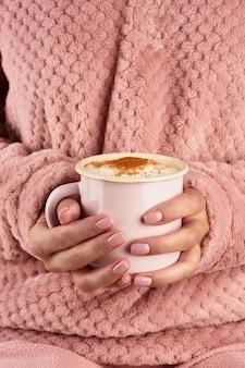 Chocolate quente da manhã em uma manhã fria de outono, mãos segurando uma caneca com uma bebida, ambiente aconchegante