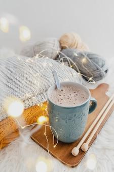 Chocolate quente de alto ângulo na tábua de madeira com cobertor e luzes