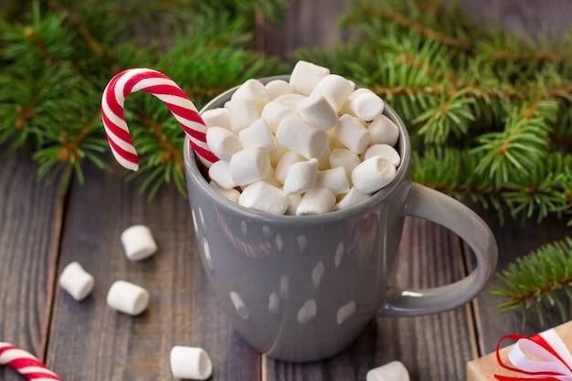 Chocolate quente de café com marshmallow na superfície da mesa de madeira rústica, bastões de doces caixas de presente abeto