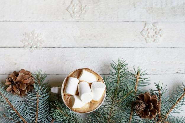 Chocolate quente de natal com marshmelow em fundo branco de madeira, decoração de galhos de árvores de natal, copie o espaço