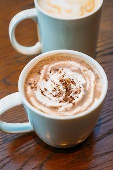 Chocolate quente e chocolate em copo branco ou caneca