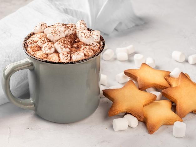 Chocolate quente em uma caneca cinza com biscoitos em uma superfície de concreto.