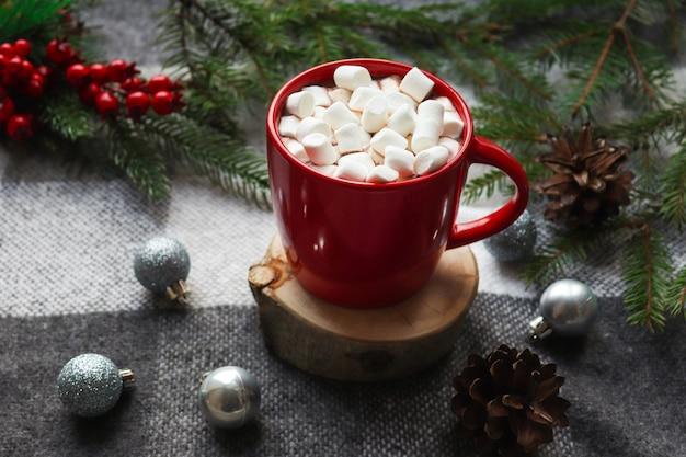 Chocolate quente em uma caneca vermelha com marshmallows em um suporte de madeira e xadrez cinza aconchegante