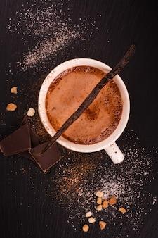 Chocolate quente em xícara de porcelana branca sobre fundo preto de pedra