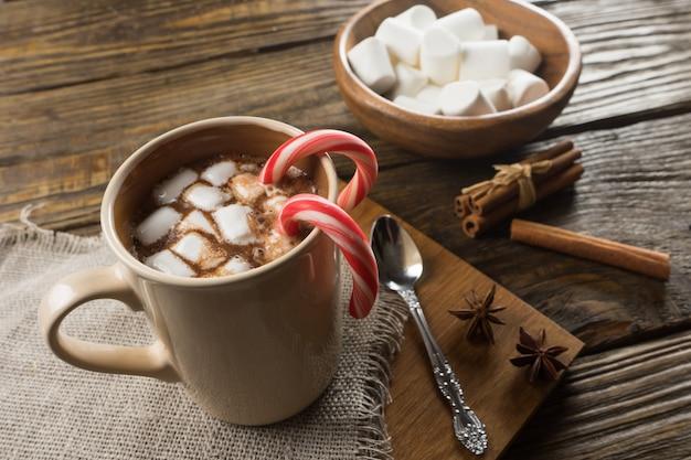 Chocolate quente, marshmallow e canela na mesa rústica