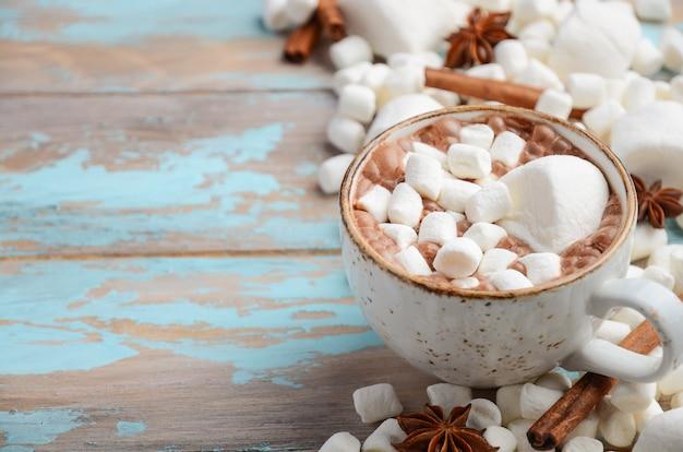 Chocolate quente, marshmallows brancos e especiarias de inverno no fundo de madeira azul