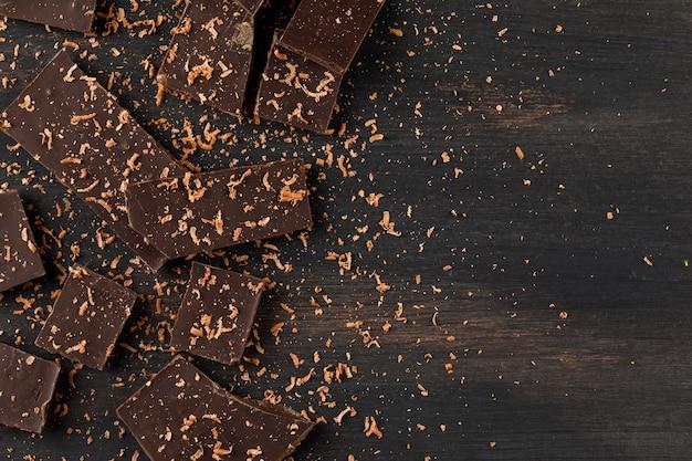 Chocolate ralado com barras de chocolate no fundo escuro, configuração plana.