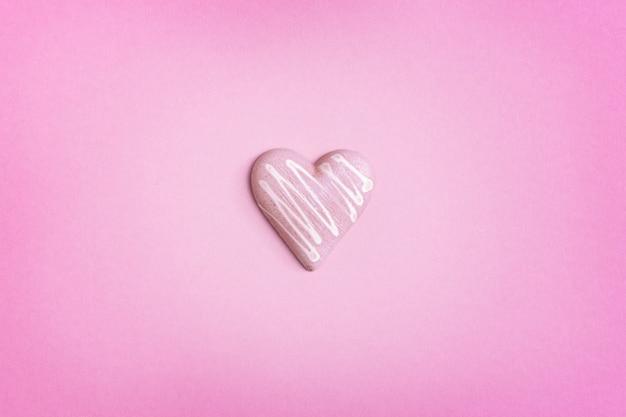 Chocolate rosa em forma de coração no fundo rosa. fundo de férias com espaço de cópia para dia dos namorados. conceito de amor