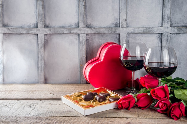 Chocolate, rosas, copos de vinho e caixa de coração na mesa de madeira
