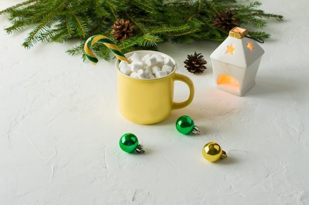 Chocolate sujo ou cacau de natal em uma caneca de cerâmica amarela com iogurte e caramelo em um fundo branco com ramos de abeto e uma vela.