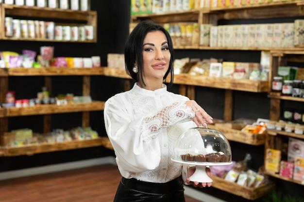 Chocolates artesanais em uma bandeja sob uma tampa de vidro nas mãos de uma bela jovem na loja