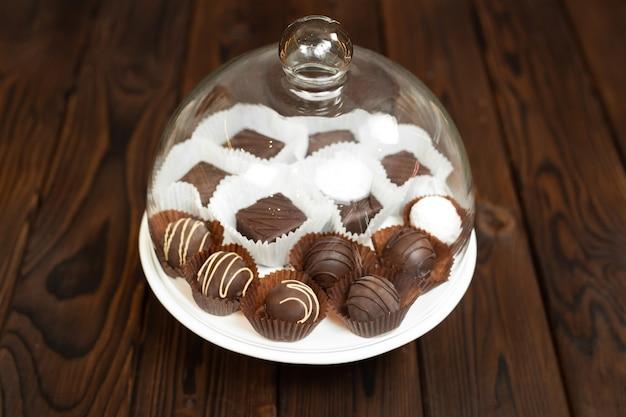 Chocolates artesanais em uma bandeja sob uma tampa de vidro