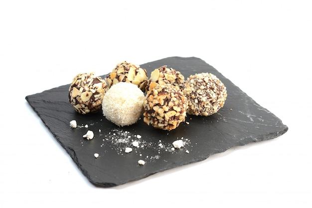 Chocolates artesanais sortidas na placa de pedra preta, em branco