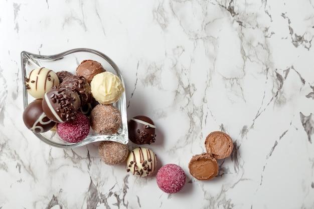 Chocolates coloridos em uma tigela de vidro no fundo de mármore branco.