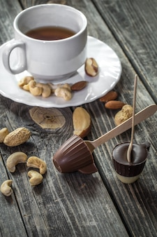 Chocolates com chá e nozes em fundo de madeira
