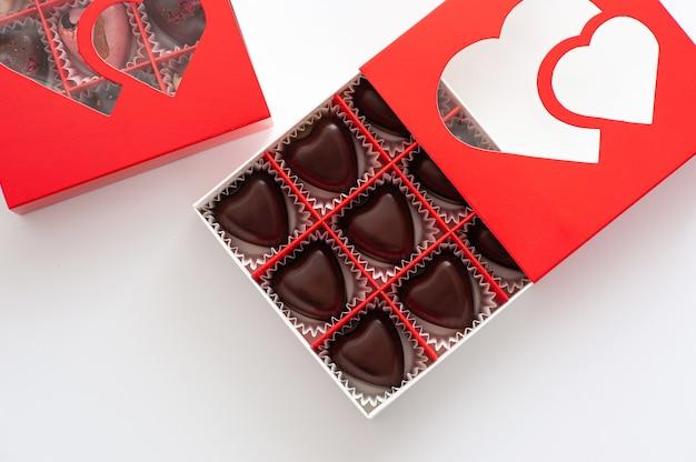 Chocolates, corações com frutas vermelhas, feitos à mão em uma linda caixa de papelão vermelha, close-up