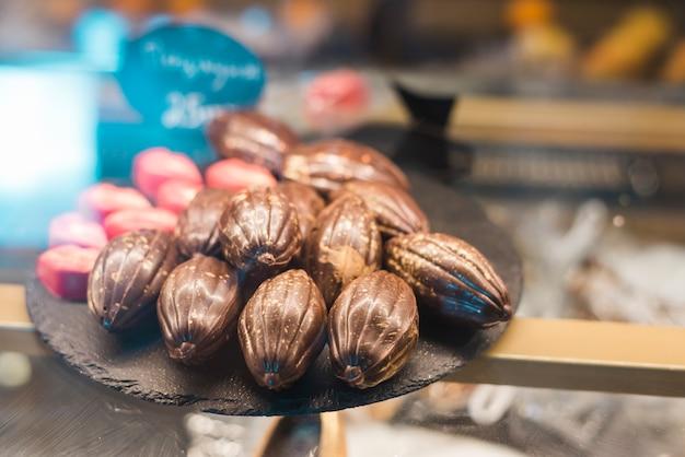 Chocolates de forma de fruta cacau na bandeja de pedra no armário de vidro