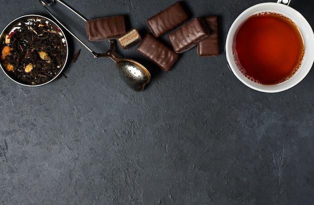 Chocolates e chá preto com ervas. coador de chá de metal.