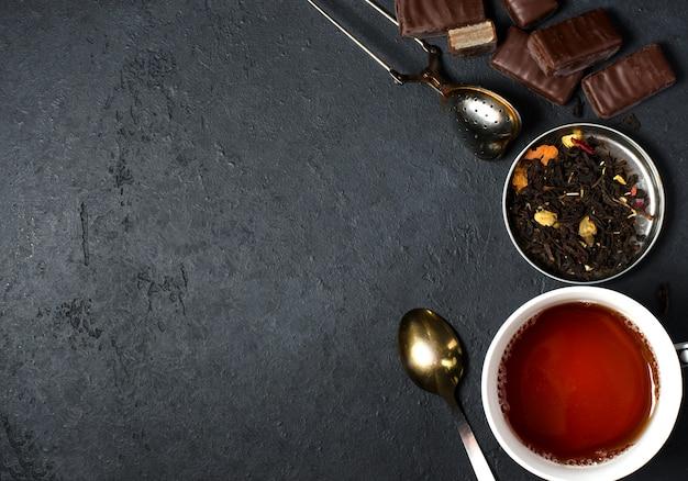 Chocolates e chá preto com ervas. filtro de chá de metal, colher.