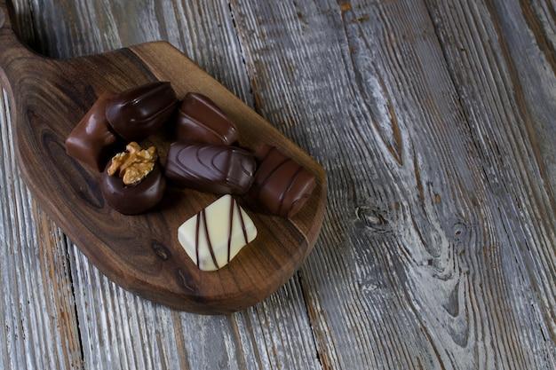 Chocolates em diferentes formas e cores sobre placa de madeira rústica. foto de comida atmosférica