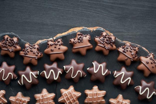 Chocolates em forma de estrela na mesa de madeira escura