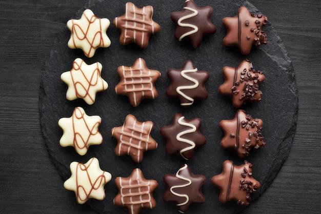Chocolates em forma de estrela no plano de fundo texturizado escuro