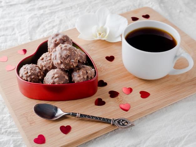 Chocolates em um coração vermelho em uma bandeja de madeira orchid do copo de café.