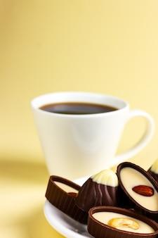 Chocolates em um prato branco e uma xícara de chá