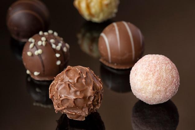 Chocolates redondos em uma superfície de espelho. doces de chocolates diferentes