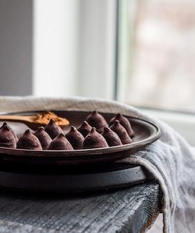 Chocolates trufados com uma xícara de café e creme no escuro