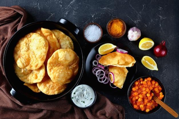 Chole bhature, uma combinação popular de pão frito com fermento e curry de grão de bico em uma mesa de concreto com limão