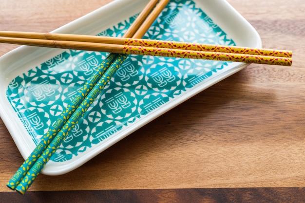 Chopsticks de bambu natural e placa no fundo da mesa de madeira