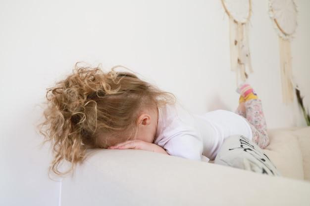 Chorando a menina da criança triste encontra-se no sofá. conceito de luto infantil.