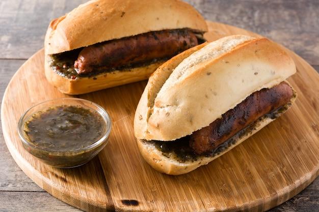 Choripan. sanduíche tradicional da argentina com molho de chouriço e chimichurri na mesa de madeira