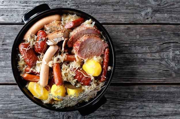 Choucroute garnie francês de couve azeda com bacon defumado, lombo de porco, salsichas de batata e tomilho guisado