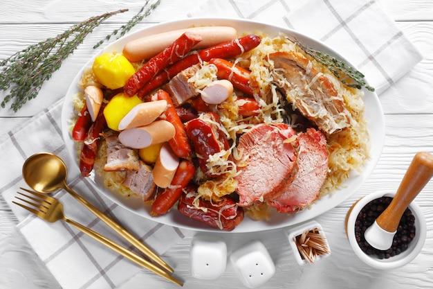 Choucroute garnie guisado de couve azeda da alsácia com linguiça defumada, lombo de porco, bacon cozido com batata em vinho branco