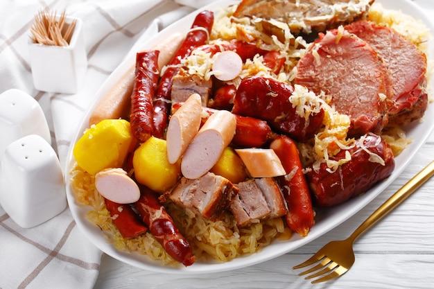 Choucroute garnie one -pot refeição francesa: ensopado de couve azeda com quatro tipos de carne de porco, linguiça defumada