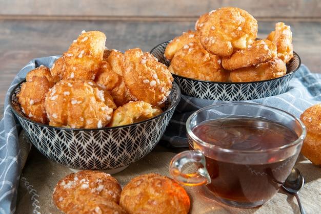 Chouquette, pastelaria francesa choux e chá na mesa de madeira