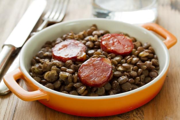 Chouriço com lentilha no prato e copo de água