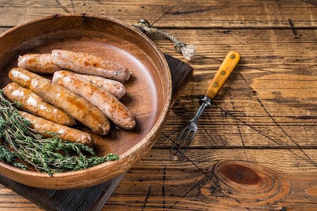 Chouriço frito e salsichas de bratwurst em prato de madeira