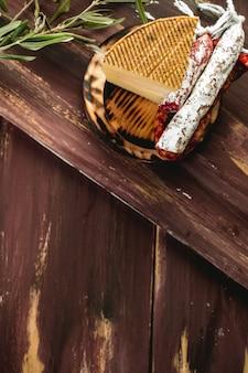 Chouriço fuet curado, queijo, salsicha da espanha. lanche de salsicha de salame. copie o espaço. mesa de madeira.