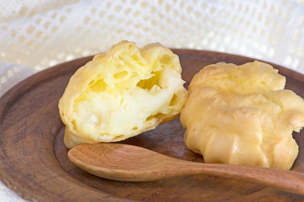 Choux pães ou eclair no prato de madeira e crochê