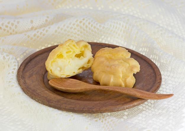 Choux pães ou eclair no prato de madeira e fundo branco de crochê