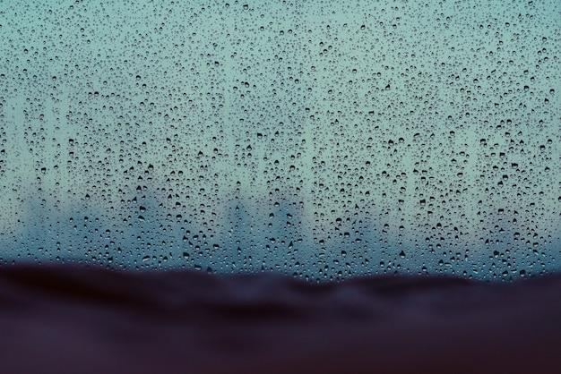 Chova a gota na janela de vidro na estação da monção com a cobertura borrada no fundo da cama e da cidade.