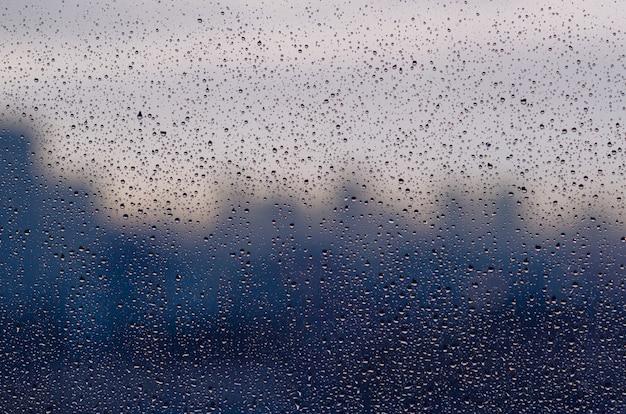 Chova a gota na janela de vidro na estação da monção com fundo borrado da cidade.