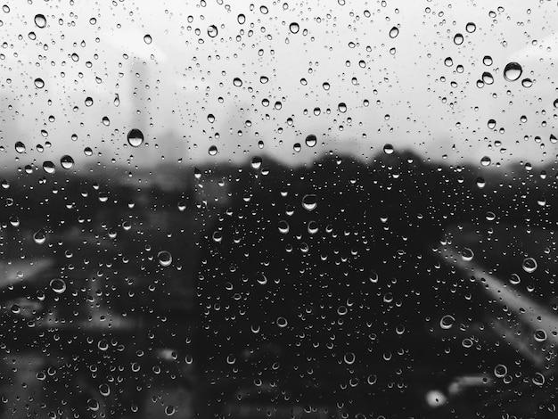 Chova gotas na superfície dos vidros de janela com nebuloso.