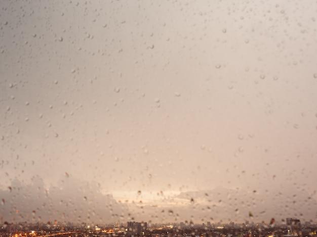 Chova gotas nas janelas com foco na arquitectura da cidade e em nuvens escuras.