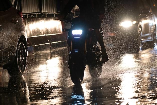 Chove na cidade nas ruas com carros e motos.