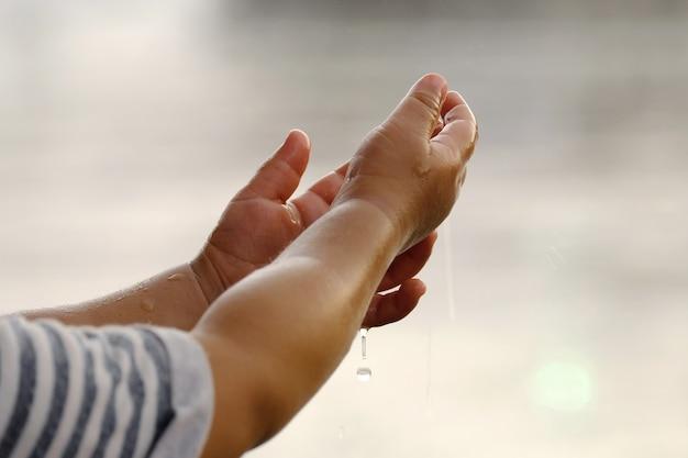 Chovendo nas mãos das crianças.
